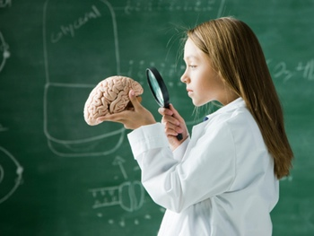 girl in a classroom standing in front of a chalkboard looking at a brain with a magnifying glass